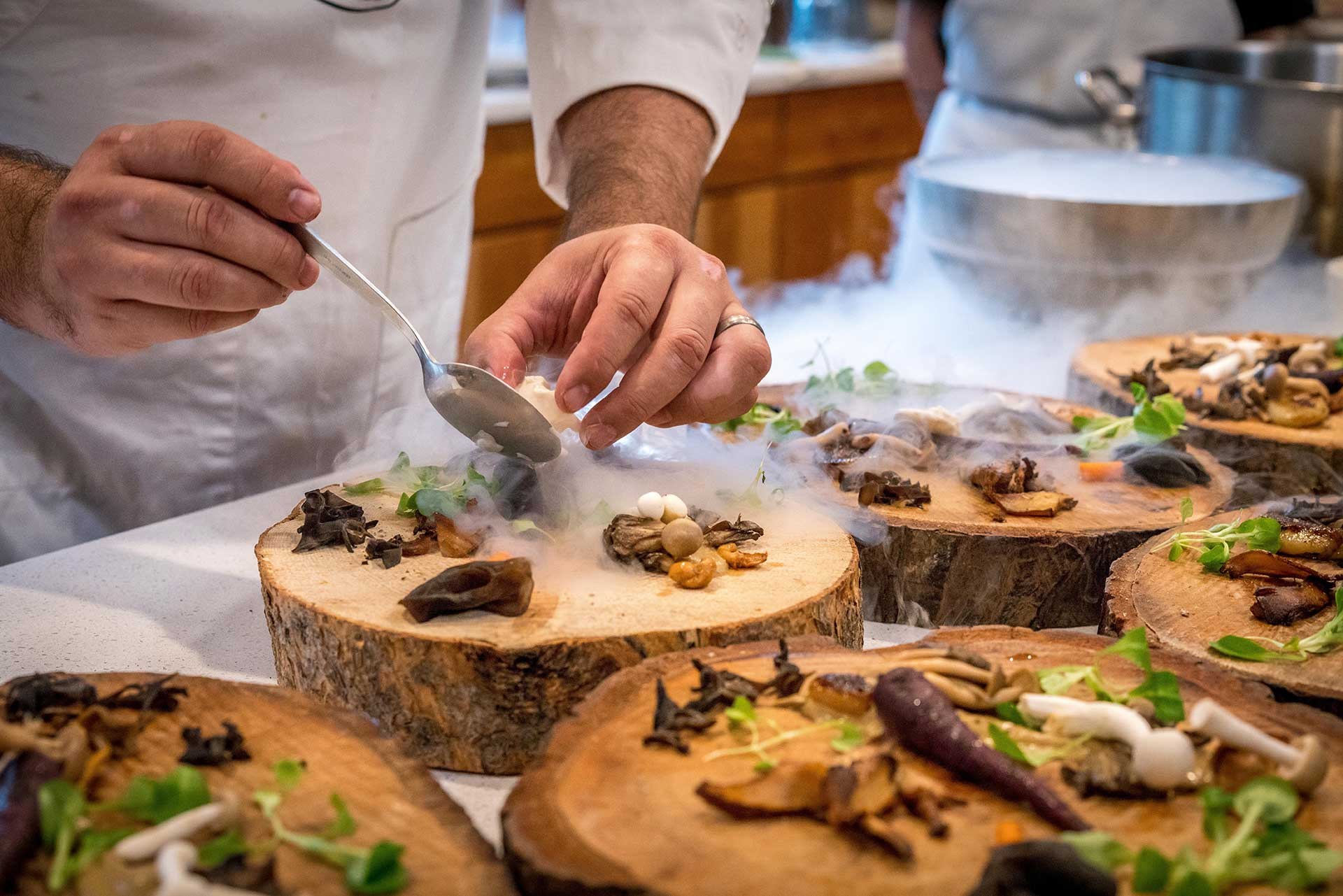 chef plating up food in a commercial kitchen
