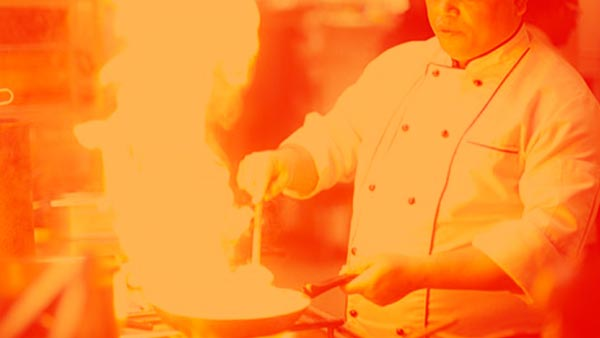 Chef cooking over a flaming stove