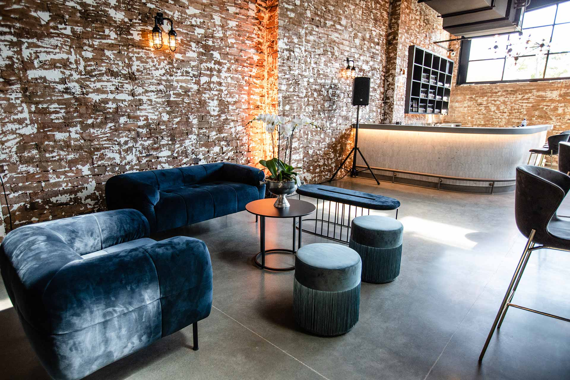 Blue velvet lounge area with bar in warehouse space
